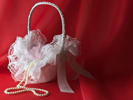 flower basket: bridal white flower basket with pearl beads over red drapery