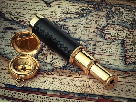 traveling theme: vintage telescope and compass at antique (17 century) map  photo
