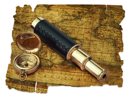 traveling theme: vintage telescope and compass at antique (17 century) map over white photo