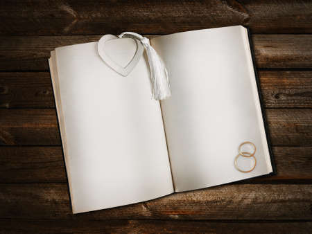 open empty book with heart shaped bookmark and golden wedding rings over wooden background photo