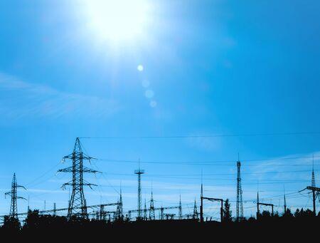 Silhouette of electric power plant agaist blue sky photo
