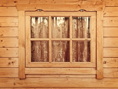 wooden facade: Window with curtains in the wooden wall Stock Photo