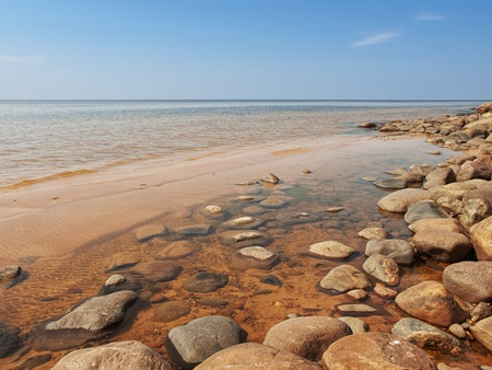 Sea rocky beach in sunny day, blue sky Stock Photo