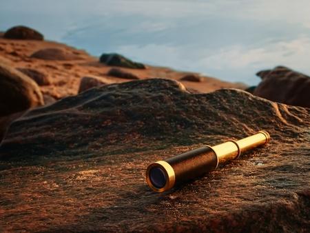 antique brass telescope at sea coast stone Archivio Fotografico