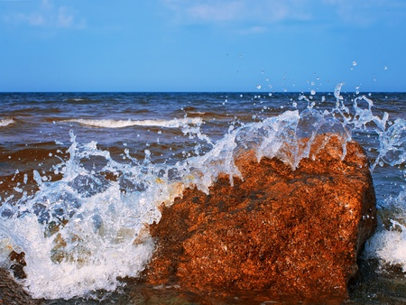 water splashes over the red rocks against blue sky Stock Photo - 10418417