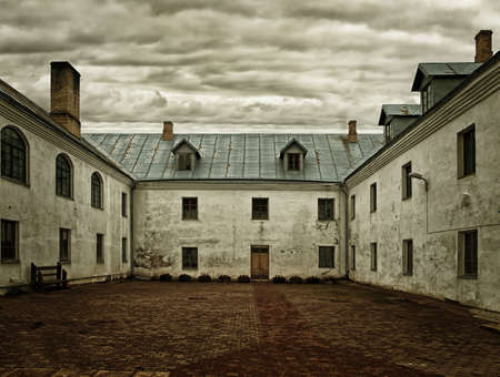 ancient prison: The courtyard of the monastery under a dark sky Stock Photo