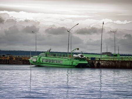 berth: quayside with green hydrofoil near it Stock Photo
