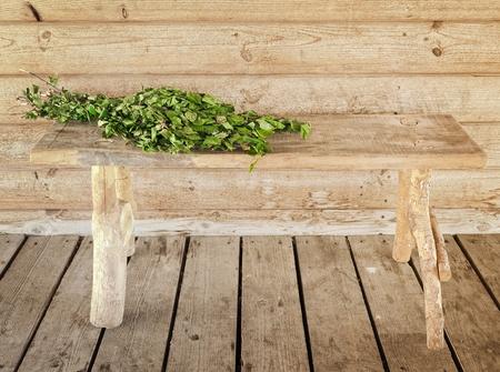 badhuis: bank en bezem over het tegen houten wand