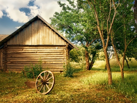 log cabin: country yard with trees, wheel and plough Stock Photo