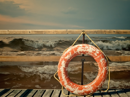 Storm at the sea, pier with life buoy