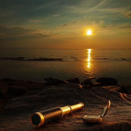 ir�ny: antik réz teleszkóp és iránytű a tengeri partjainál kőből Stock fotó