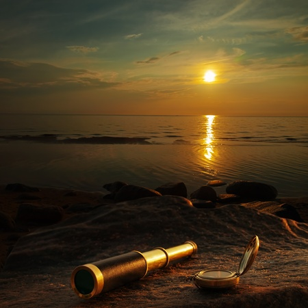 spyglass: antique brass telescope and compass at sea coast stone