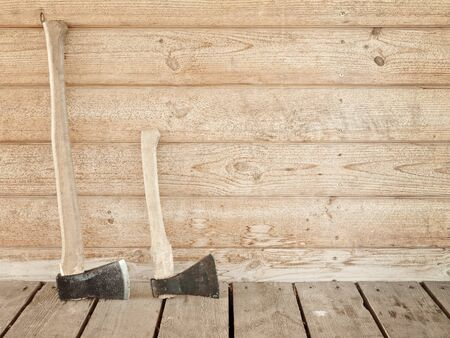 woodgrain: two old axes near the wooden wall Stock Photo