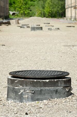 repaired: manhole on the background of the road being repaired