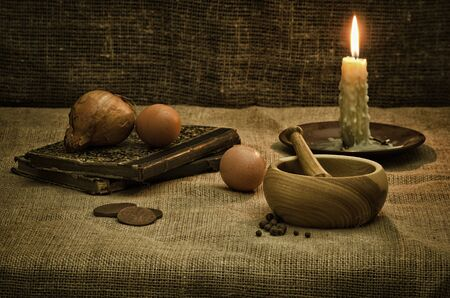 Rural still life with mortar,candle,books and eggs Stock Photo - 14095557