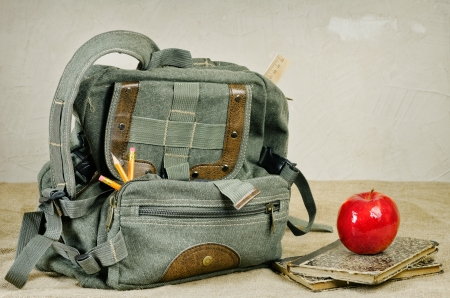 bookbag: Still life with an old backpack, books and red apple  Stock Photo