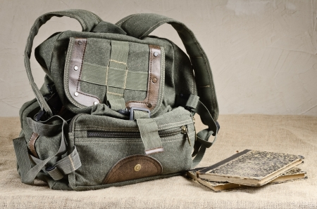 haversack: Tarpaulin backpack and old books on the canvas