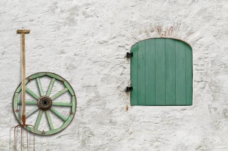 hayfork: Hayfork And Wooden Wheel Near The Wall Of Farmer