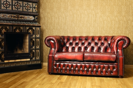 Old Red Genuine Leather Sofa Near The Fireplace photo