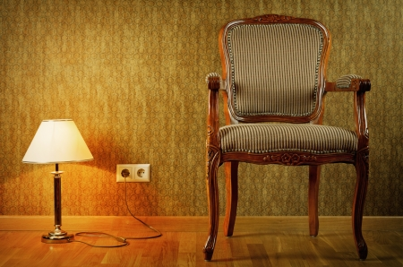 easy chair: Turned On Lamp And Armchair Near The Wall
