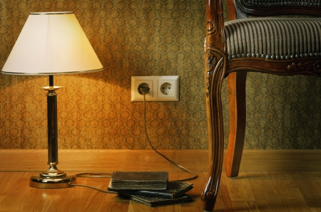 Turned On Lamp And Part Of Armchair Near The Wall photo