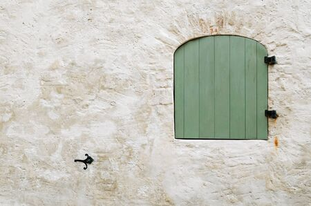 unevenness: Closed Green Wooden Window Shutters In The Wall