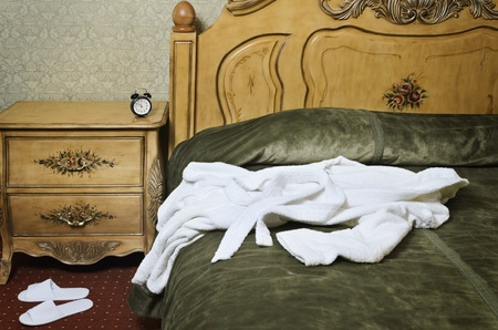White Bathrobe On The Old Antique Bed photo