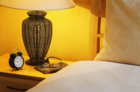 bedchamber: Close Up Fragment Of The  Bedroom With Reading Lamp And Alarm Clock Stock Photo