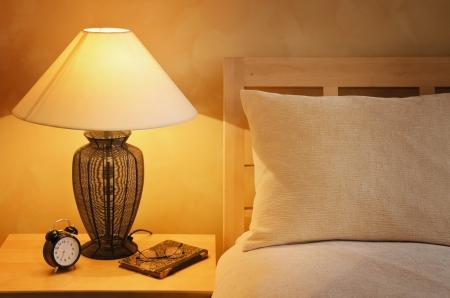 Close Up Frammento della camera da letto con lampada da lettura E Sveglia Archivio Fotografico