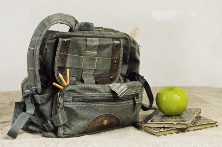 knapsack: Back To School Theme  Retro Backpack And Apple On The Old Books Stock Photo