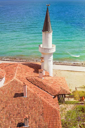 architectural exteriors: Tiled Roof with Minaret against the Sea Stock Photo