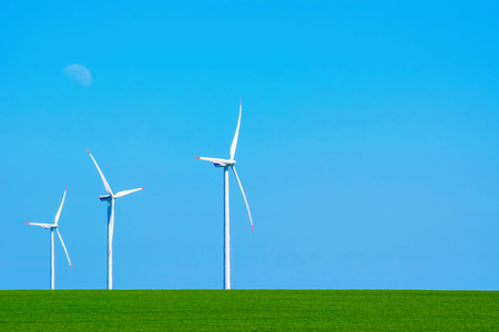 grassplot: Three Wind Turbines in heat haze against of Blue Sky Stock Photo