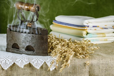 osnaburg: Old Hot Iron and Bunch of Oats on the Table Stock Photo