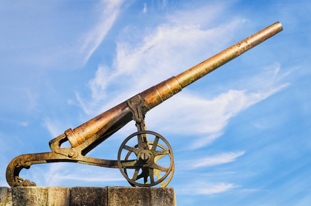 armament: Old Cannon against the Blue Sky Stock Photo
