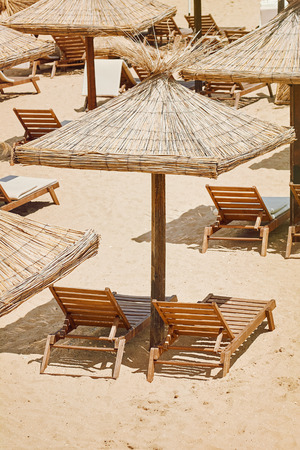 thatched: Umbrellas and Sun Loungers on the Beach Stock Photo