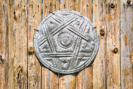ligneous: Old Shield on the Wooden Fence Stock Photo