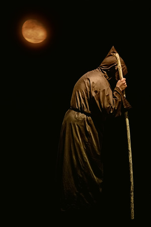 monk robe: Monk with a Stick at Night Stock Photo