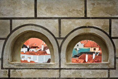 loopholes: View on Houses of Cesky Krumlov through the Loopholes of the Fortress Wall Stock Photo