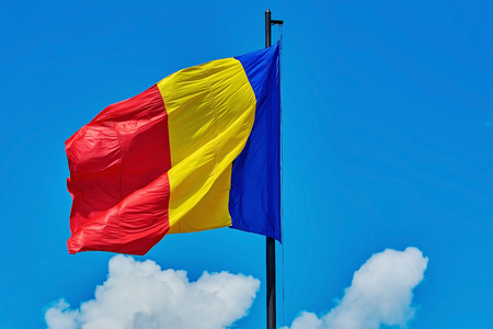 Flag of Romania against Blue Sky with Clouds
