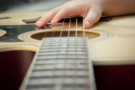 musical instruments: Macro shot down the fretboard of acoustic guitar with shallow depth of field