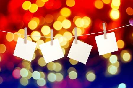 Blank paper cards hanging on clothespins against Christmas lights background Standard-Bild