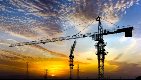 unfinished building: Industrial construction cranes and building silhouettes over sun at sunrise