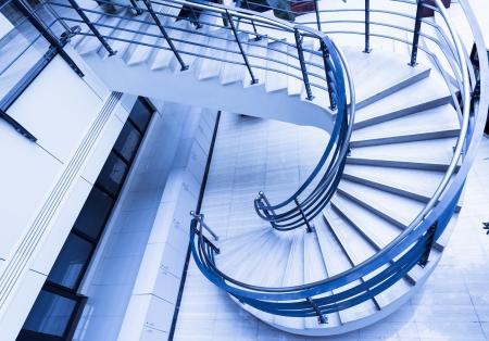 Sleek metal spiral staircase, modern architectural interior decoration