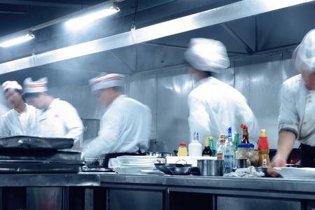 chefs whites: motion chefs of a restaurant kitchen