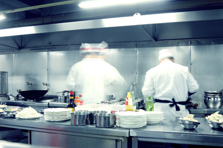 busy restaurant: motion chefs of a restaurant kitchen