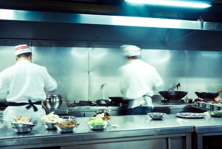 busy restaurant: motion of chefs in the restaurant kitchen Stock Photo