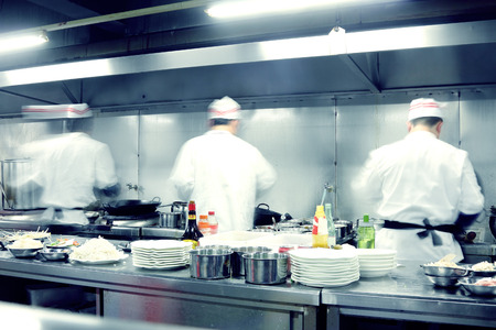busy restaurant: motion chefs in restaurant kitchen Stock Photo
