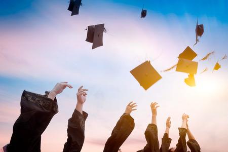 graduado: graduados que lanzan los sombreros de graduación en el aire. Foto de archivo