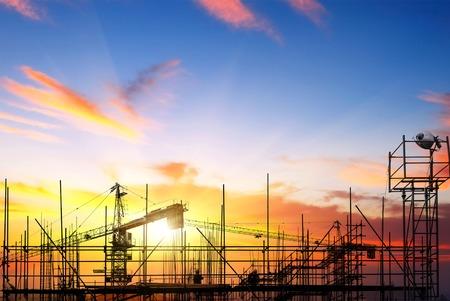 産業建設用クレーンと日の出の太陽上の建物のシルエット。