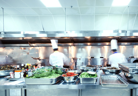 preparing food: motion chefs of a restaurant kitchen